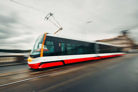 street life: Daily life in the city. Tram of the public transport on the street - blurred motion