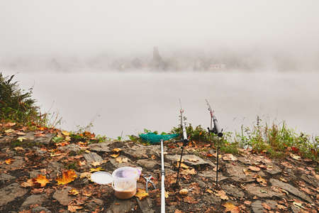 Fishing rods, landing net and bait fishing on the river bank. Thick fog during autumn morning in beautiful nature in the Czech Republic Stock Photo