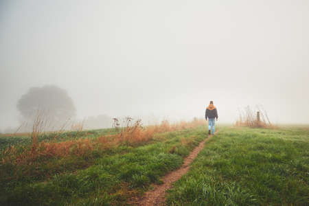 hombre solitario: Lonely young man walking in mysterious fog. Autumn morning in beautiful nature in the Czech Republic