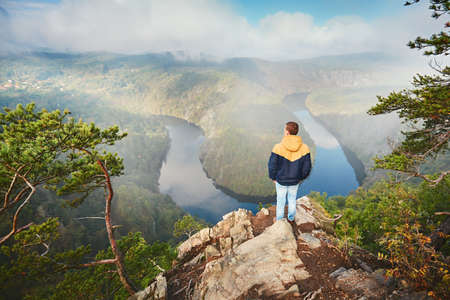 Traveler on the top of rock. Young man enjoying view on river valley in morning fog. Vltava river in Central Bohemia, Czech Republic. Stock Photo