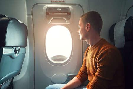 salida de emergencia: viajar cómodo en avión. joven pasajero curioso que mira desde el (la salida de emergencia de la aeronave) ventana.