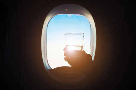 refreshment: Comfortable traveling by airplane. Passenger is holding glass of the wine during the flight.