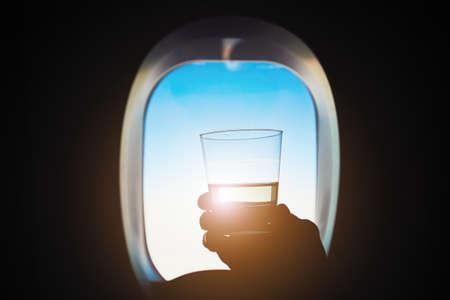 快適な飛行機の旅します。乗客は飛行中にワインのガラスを保持しています。 写真素材