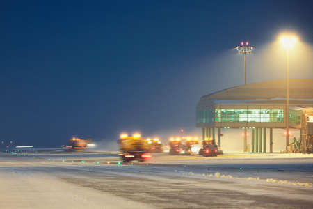 runways: Airport during the snowstorm. Snow plows cleared the snow from the runways and taxiways. - selective focus on terminal building