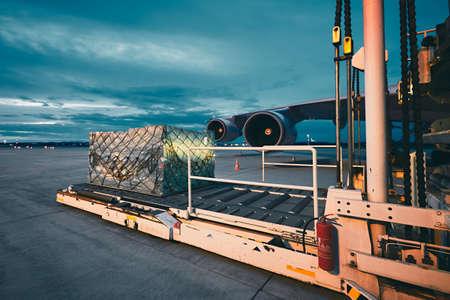 Aeroporto ao anoitecer. Carregamento de carga para a aeronave de frete.