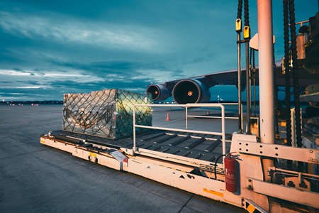 cargo: Airport at the dusk. Loading of cargo to the freight aircraft. Stock Photo