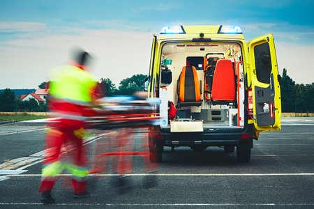 Dringende medische hulp. Paramedic trekt brancard met de patiënt naar de ambulance auto. Stockfoto - 65695568