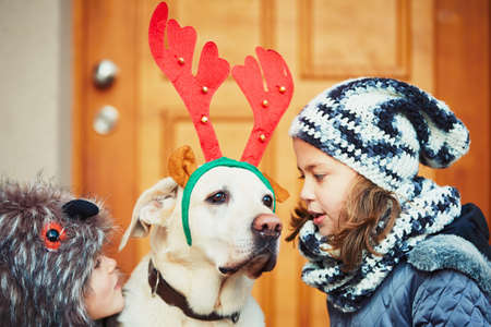 dog in costume: Christmas walk with dog. Two girl are going out with labrador retriever dressed as a Christmas reindeer. Stock Photo