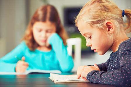 Piccoli fratelli con i libri di scuola stanno facendo i compiti per la scuola elementare.