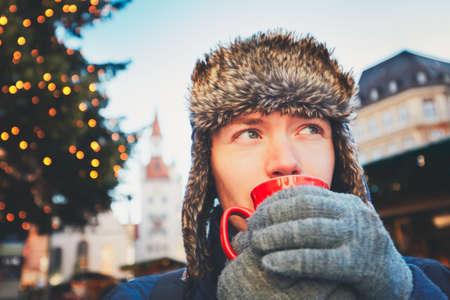 vin chaud: Jeune homme de boire du vin chaud (ou coup de poing ou de thé ou de café) de tasse rouge au marché de Noël - Munich, Allemagne
