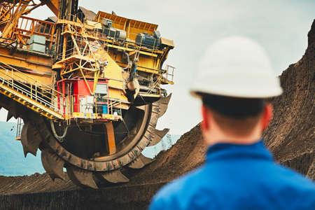 Mineração de carvão em um poço aberto. Mineiro, olhando para a enorme escavadeira. Indústria na República Tcheca, Europa