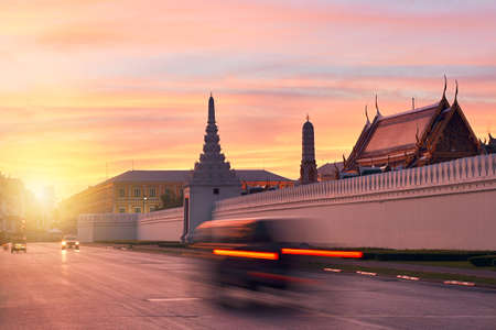 Tuk Tuk taxi in blurred motion in front of Grand Palace during beautiful sunrise  Bangkok, Thailand