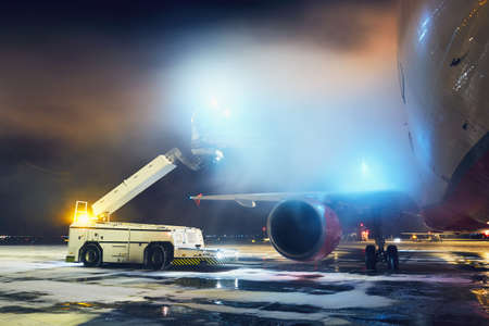 Airport in winter. Deicing of the airplane before flight. Editorial