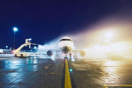 glycol: Airport in winter. Deicing of the airplane before flight. Stock Photo