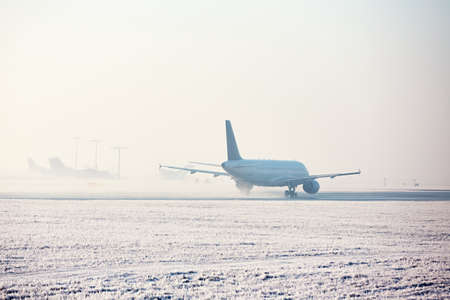 Airport in winter. Airplane is taking off in frosty day. Фото со стока