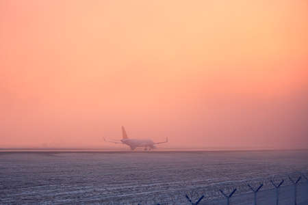 industry moody: Freezing fog at the airport. Airplane taking off during golden sunset. Stock Photo