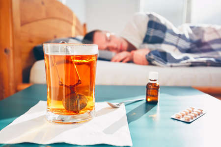 sleeping pills: Sick man is lying in bed under blanket. Selective focus on the hot tea and medicine on the table.