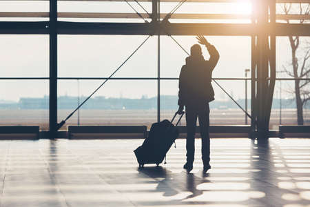 Saying goodbye at the airport. Silhouette of the traveler waves his hand. Standard-Bild