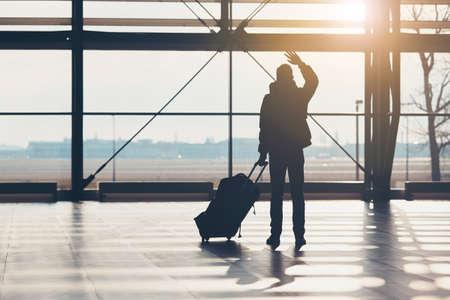 Pożegnaj się na lotnisku. Sylwetka podróżującego faluje ręką.