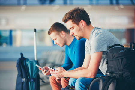 Two friends traveling together. Travelers with mobile phones waiting at the airport departure area for their delay flight. Imagens