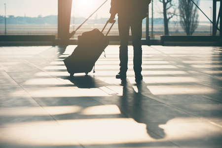 Shadow of the traveler with luggage at the airport. Archivio Fotografico