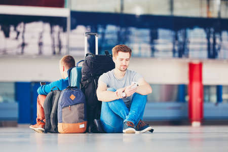 Two friends traveling together. Travelers with mobile phones waiting at the airport departure area for their delay flight. Stock Photo