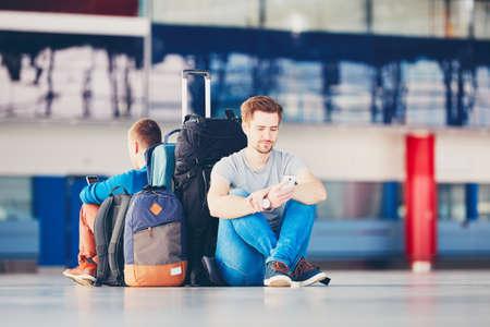 Deux amis qui voyagent ensemble. Les voyageurs avec des téléphones mobiles en attente dans la zone de départ de l'aéroport pour leur vol de retard.