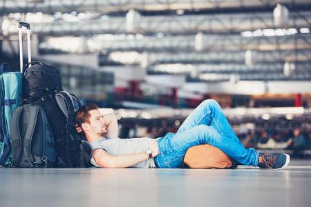persona viajando: Viajeros esperando en la zona de salida del aeropuerto para su vuelo de retardo.