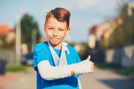 Mischievous boy with broken hand injured after accident showing OK sign Stock Photo