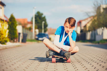 Mischievous boy with broken hand injured after accident on skateboard. Stock Photo