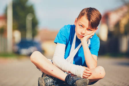 Mischievous boy with broken hand injured after accident during summer sports. Stock Photo