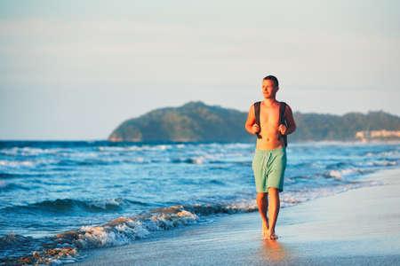 若者のバックパックを美しいビーチの上を歩きます。 写真素材