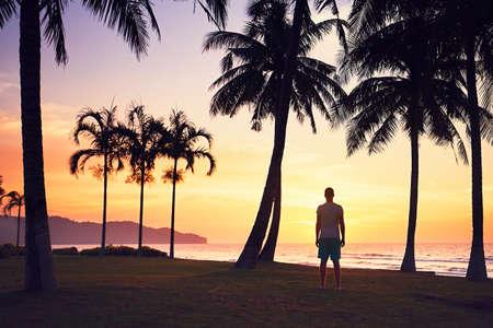 熱帯のビーチにすばらしい夕日を見ている男。ボルネオ島、マレーシア。