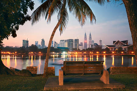 Beautiful morning in public park in Kuala Lumpur. Skyline of the modern city at sunrise.