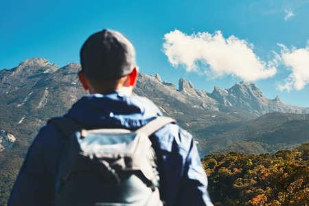 山でバックパックを持つ男。マレーシアのキナバル山に登る若い旅行者。