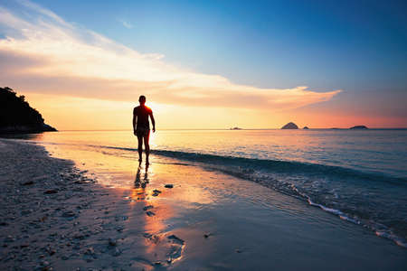 Lonely man walking on the tropical beach during amazing sunset. Perhentian islands, Malaysia Stock Photo