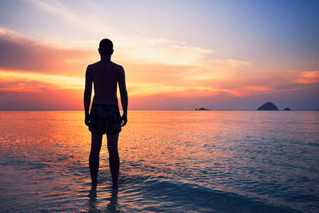 Pensive young man standing in water of the tropical sea during beautiful sunset.
