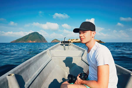 Idyllic vacation. Young photographer with dslr camera traveling by boat.