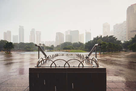 Rain in the city - public park and skyline of the Kuala Lumpur, Malaysia