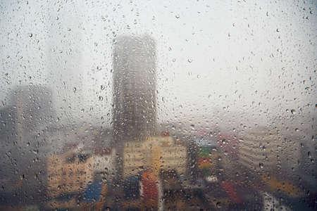 Lluvia en la ciudad y enfoque selectivo en las gotas - Skyline of the Kuala Lumpur, Malaysia Foto de archivo - 76439568