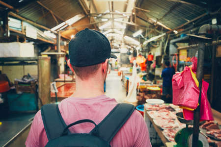 Young traveler with backpack in food market in Chinatown - Kuala Lumpur, Malaysia Stock Photo