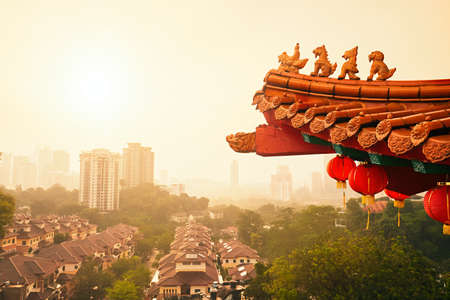 Roof of the Thean Hou Temple and Kuala Lumpur skyline after rain during sunset, Malaysia