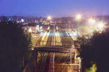Red tail lights of the express train in railway station at night. Chocen, Czech Republic Stock Photo