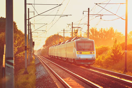 Traveling by modern passenger train. Railway at the beautiful sunset (golden hour). Stock Photo