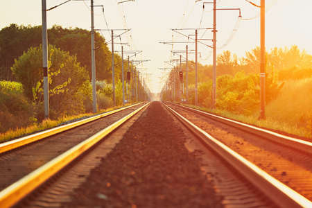 Railway at the amazing sunset (golden hour). Modern railroad track in landscape. Stock Photo