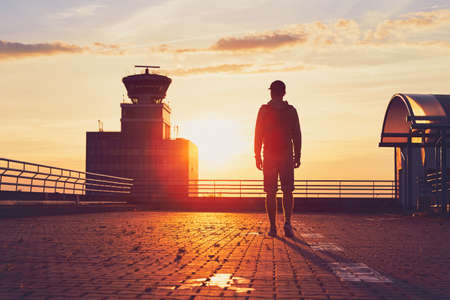 Traveler at the airport. Air Traffic Control Tower at the amazing sunset. Prague, Czech Republic Stock Photo