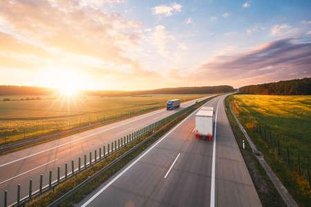田舎の真ん中に高速道路での素晴らしい日の出。交通機関や車のテーマです。