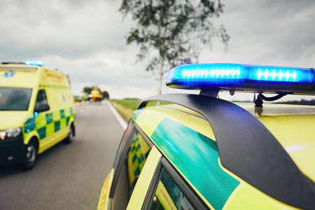 Ambulance cars. Teams of the Emergency medical service are responding to an traffic accidnet in bad weather.