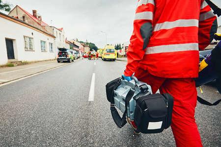 Mano del médico con desfibrilador. Los equipos del servicio médico de emergencia están respondiendo a un accidente de tráfico.