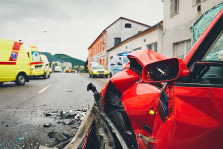 Close-up view at a crashed car. Teams of the Emergency medical service are responding to an traffic accident. - selective focus